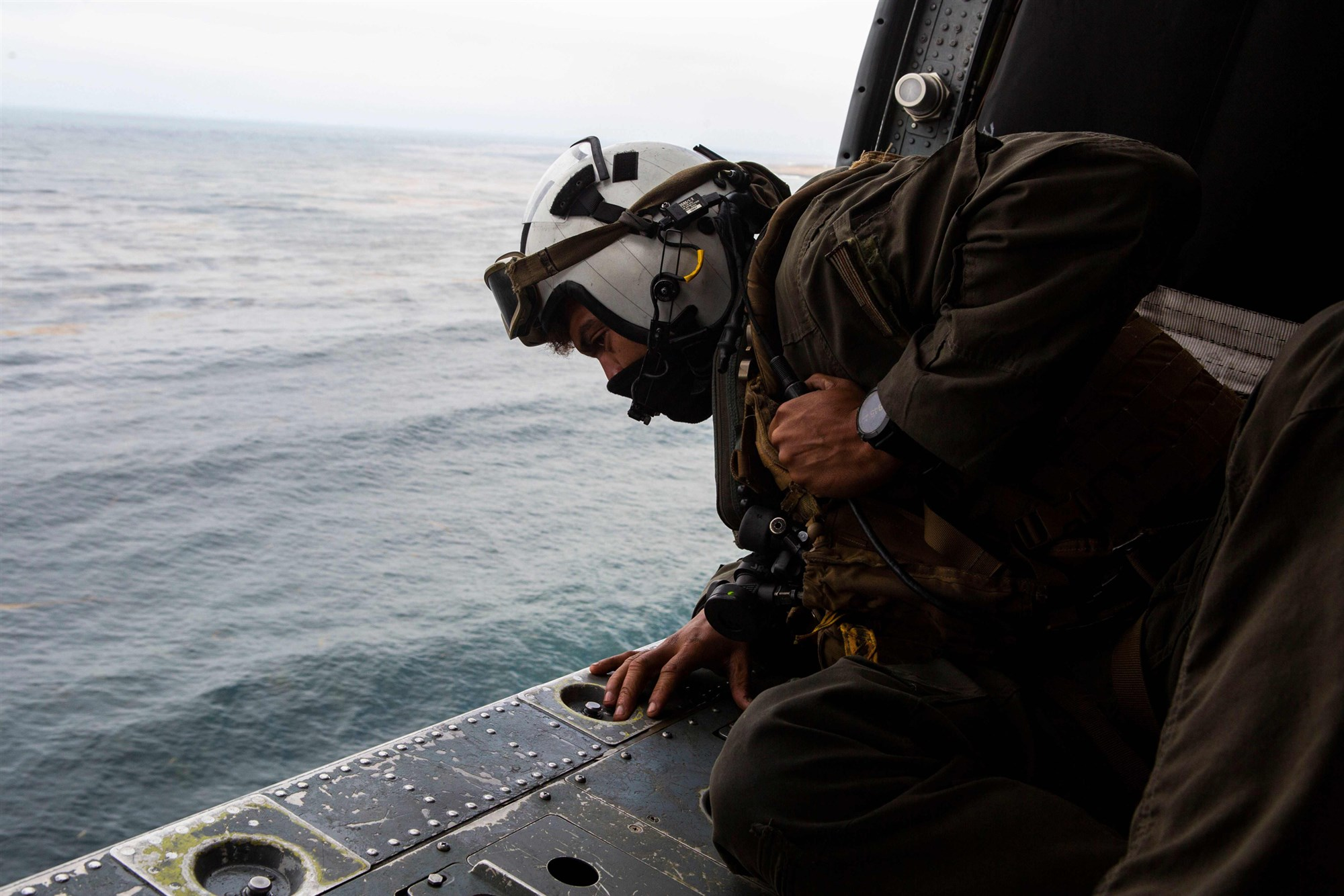 This US Marine Corps handout photo shows Naval Air Crewman 2nd Class Joseph Rivera, a search and rescue swimmer assigned to the amphibious assault ship USS Makin Island (LHD-8), looking out of a US Navy MH-60 Seahawk while conducting search and rescue relief operations following an AAV-P7/A1 assault amphibious vehicle mishap off the coast of Southern California on July 30, 2020.